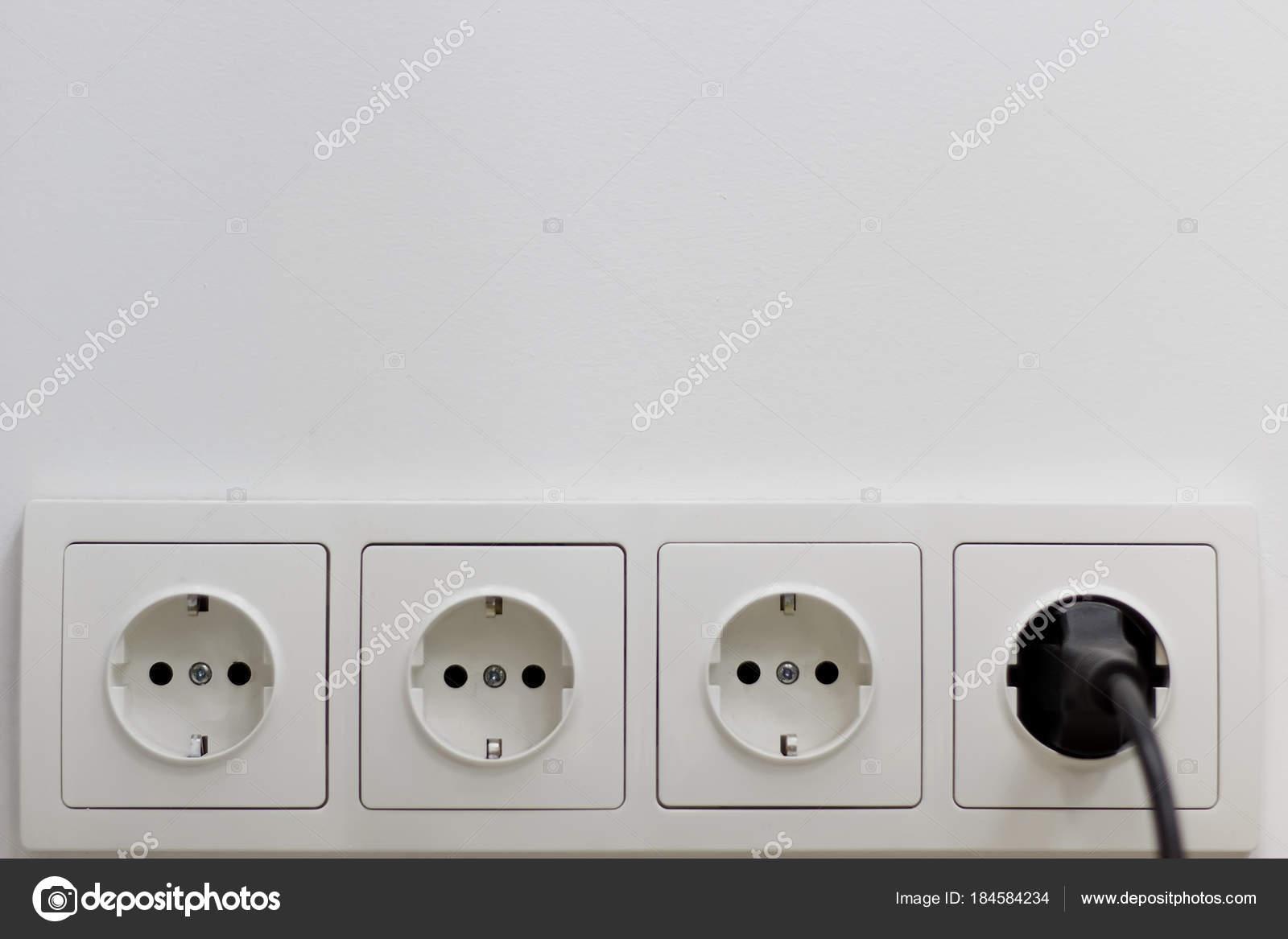 vier Anschlüsse in einer weißen Wand mit einem stecken Stecker aus ...