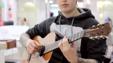 The guy plays a classical guitar in a music store, a musical mood, classical music