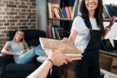 oříznuté zastřelených mladé ženy držící knihy domácí knihovna