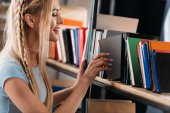 Fotografie Smiling young woman choosing book on bookshelf in library