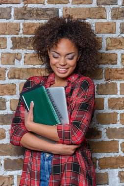 stylish african american girl smiling while holding laptop and notebook