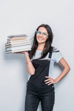 smiling caucasian girl holding books and looking at camera