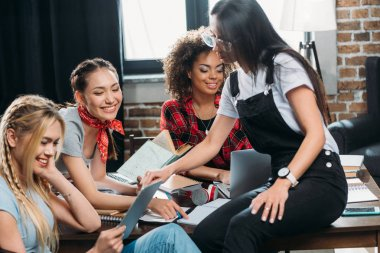 smiling multiethnic women working while sitting at table in home office