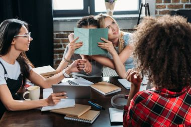 multiethnic girls working while sitting at table in home office