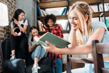 caucasian girl reading book while her friends sitting on sofa at home library