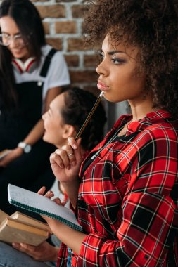 african american girl holding notebook in thoughtful pose while her friends talking