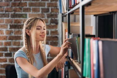 Smiling young woman choosing books on bookshelves in library