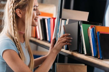 Smiling young woman choosing book on bookshelf in library