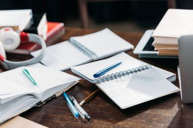 Close-up view of open blank notebooks with pens and books on wooden table