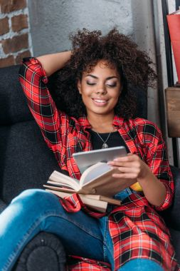 Smiling young woman sitting in chair with books and using digital tablet