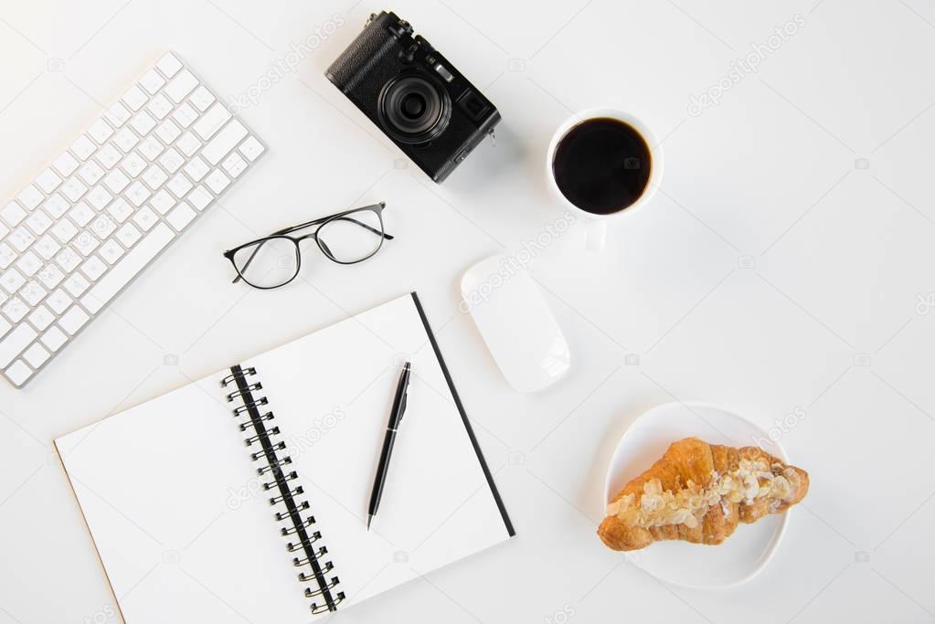 Top view of keyboard, computer mouse, eyeglasses, camera, blank notebook with pen, croissant and cup of coffee at workplace