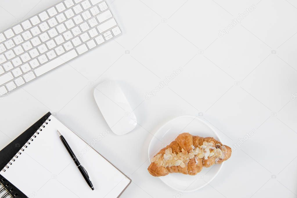 Top view of tasty croissant on plate, blank notebook with pen, keyboard and computer mouse at workplace