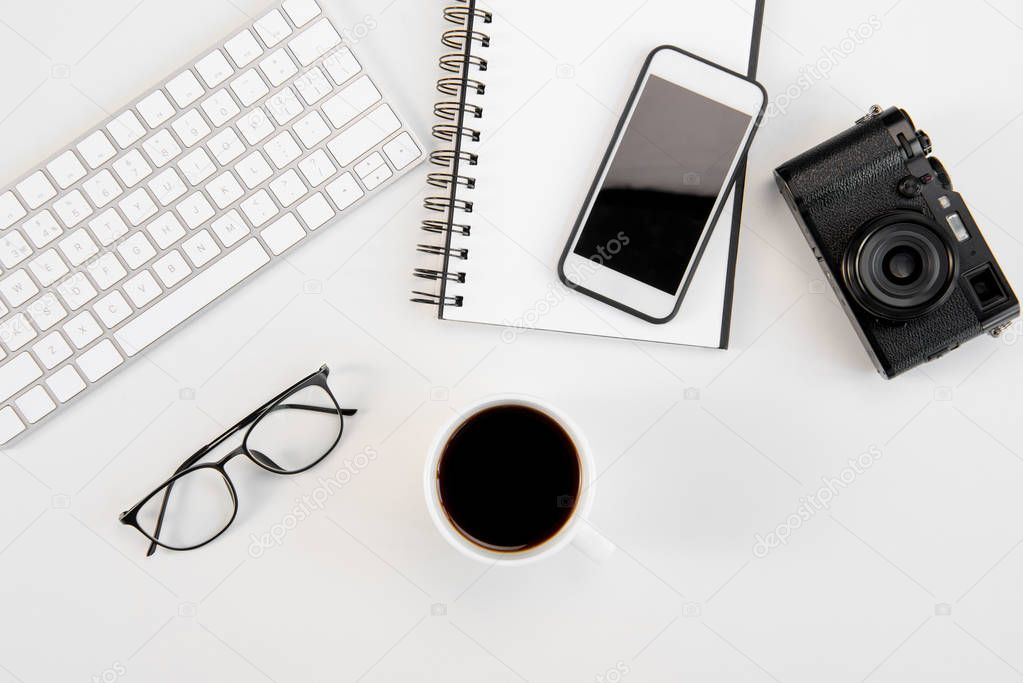 Top view of cup of coffee, keyboard, notebook, eyeglasses, smartphone and camera at workplace
