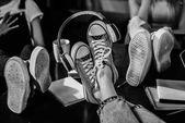 Detailní pohled ženské nohy ve stylové boty se sluchátky na dřevěný stůl, ČB Foto