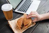 Zavřete z ruky držící burger s kávou jít a laptop na dřevěnou desku