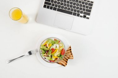 Top view of laptop, orange juice in glass and fresh healthy salad with toasts at workplace