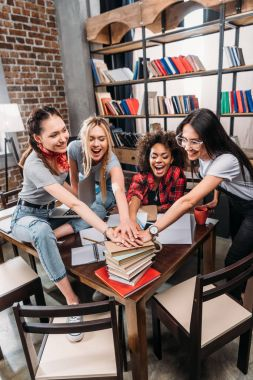 Cheerful young women stacking hands on pile of books
