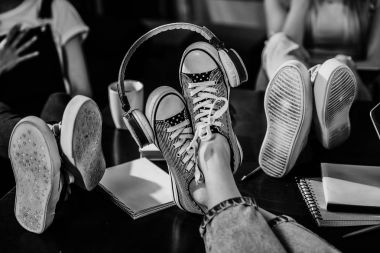 Close-up view of woman's feet in stylish shoes with headphones on wooden table, black and white photo