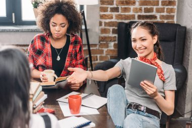 Attractive young friends drinking coffee and studying together with books and digital tablet