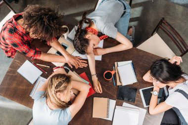 Overhead view of tired young students sleeping on table with notebooks and digital devices