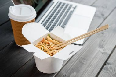 close up of noodle with chopsticks and coffee to go with laptop on wooden tabletop
