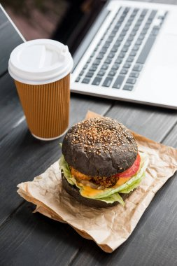 close up of burger with coffee to go and laptop on wooden tabletop