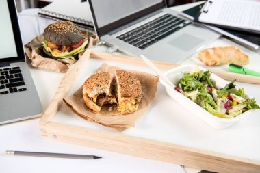 tasty burgers with fresh salad and bread loaf with laptops on tabletop