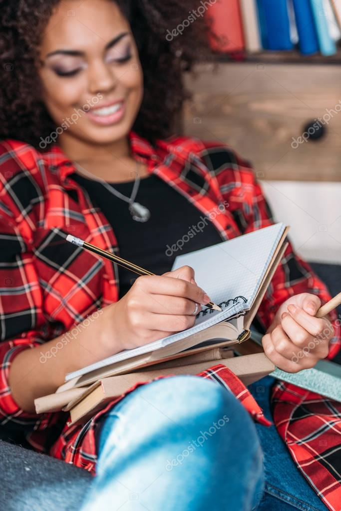 Attractive young african american student studying with books and textbooks