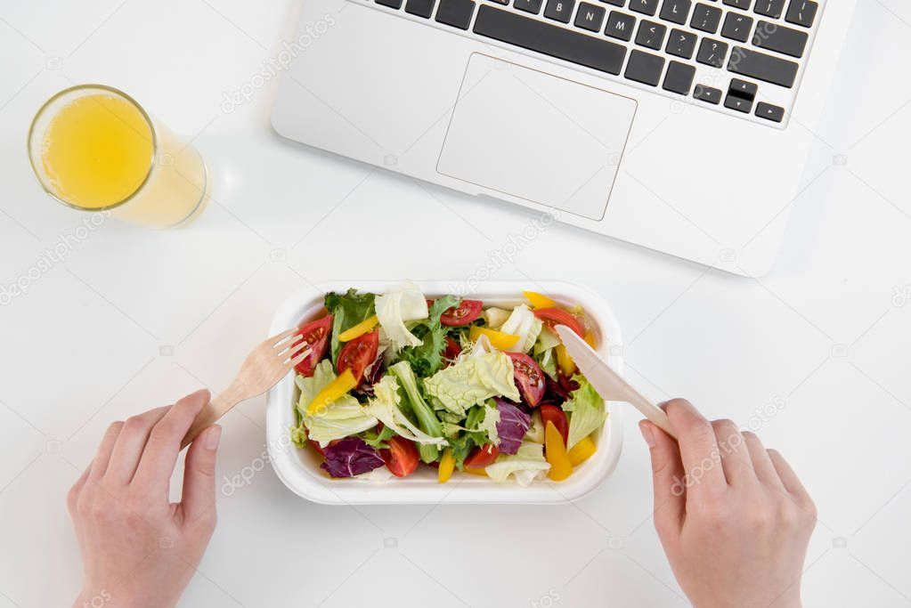 Cropped shot of person eating fresh salad and drinking orange juice at workplace with laptop
