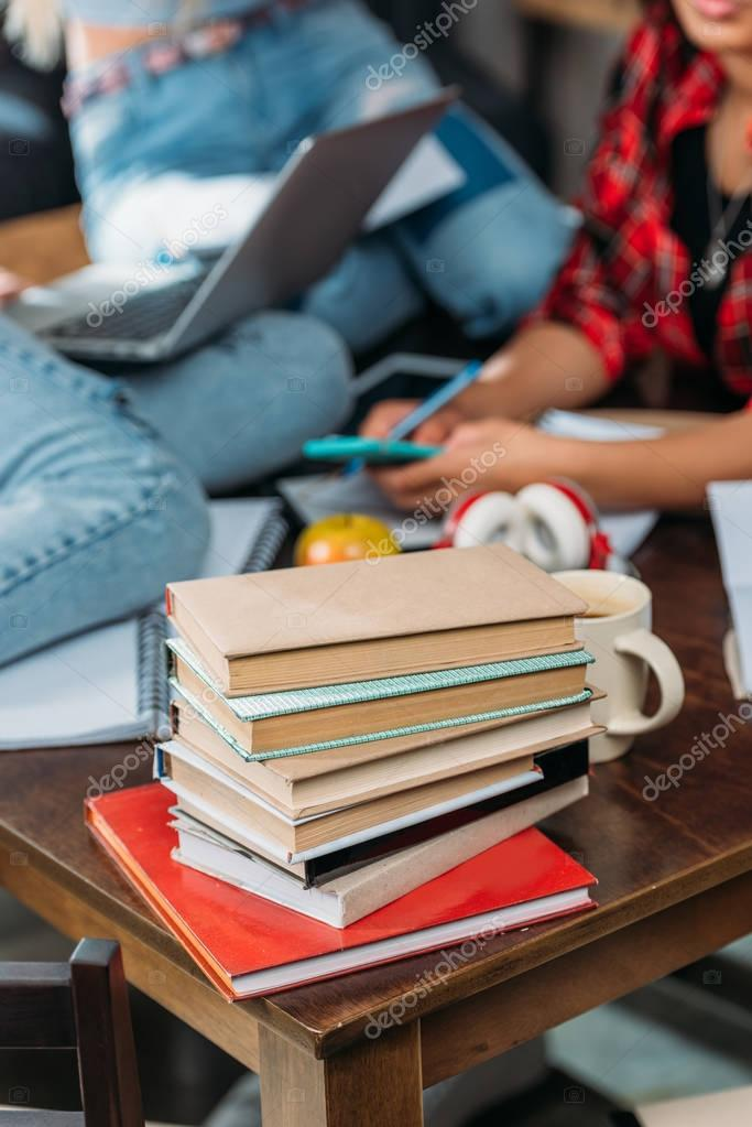 Close-up view of pile of books on wooden table and young friends sitting behind