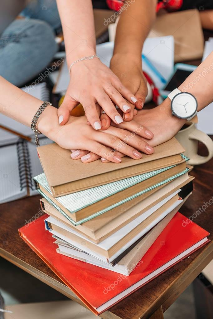 Close-up view of young women stacking hands on pile of books