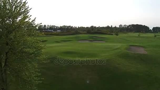 Eine Drohne fliegt über einen grünen Golfplatz