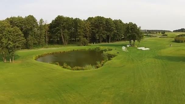 A drone flies over a green golf course. Wedding preparations