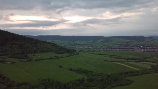 Letecký pohled na Tatranské hory se silnicí a vesnicí na pozadí při západu slunce