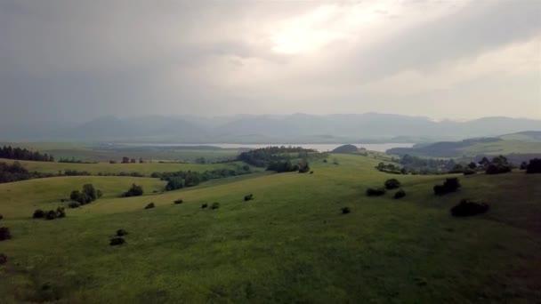 Letecký pohled na krásné, zelené pole s horami v pozadí při západu slunce