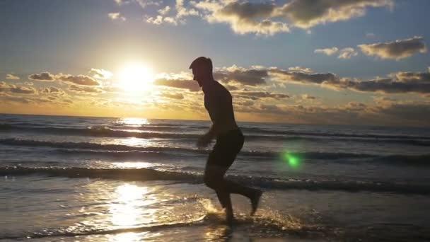 Muž běžící na vlhké písčité pláže během cvičení v pomalém pohybu