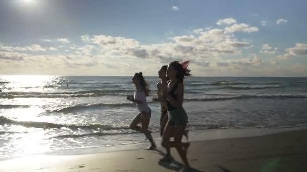 Tři nádherné ženy běh na pláži během cvičení