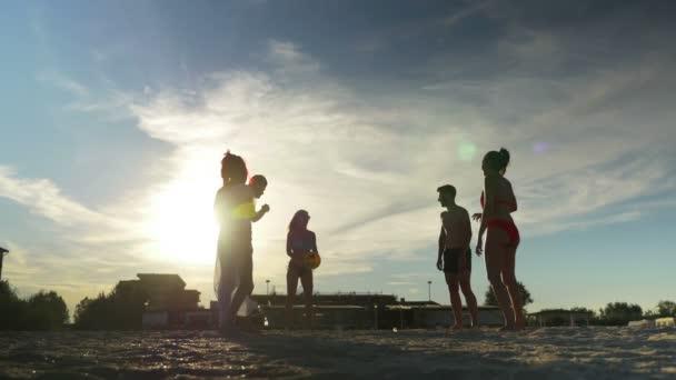 Fiatal vidám baráti röplabdázás a homokos strandon