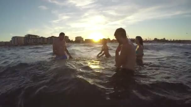Group of friends teasing one another and playing with water in the sea
