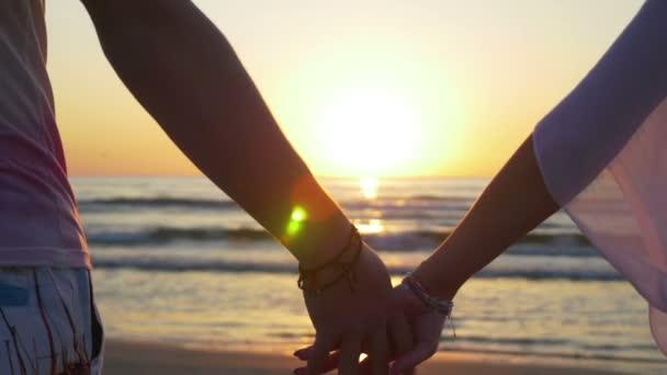 Romantický pár, drželi se za ruce a půjdete směrem k vodě na písečné pláži
