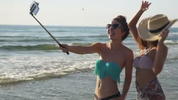 Sexy dívka přátelé při selfie na pláž a líbání