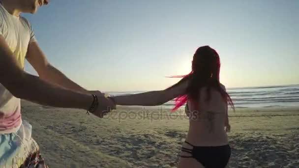 Mladý pár, drželi se za ruce a běží na pláži směrem k moři