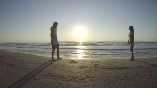 Žena běží směrem k muži a skákání v ruce na pláži