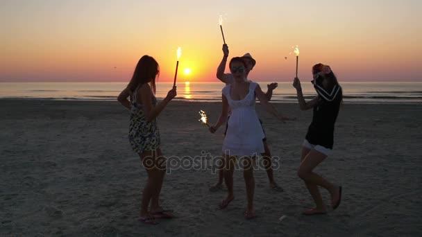 Baráti ünnepli csillagszórók, a tengerparton a napkelte
