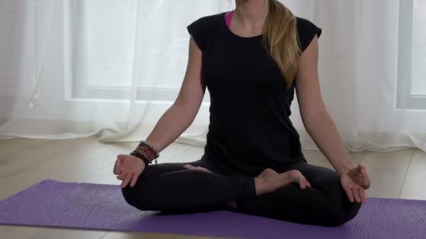 schöne erwachsene Frau meditiert in Lotus-Pose in einer Yoga-Turnhalle