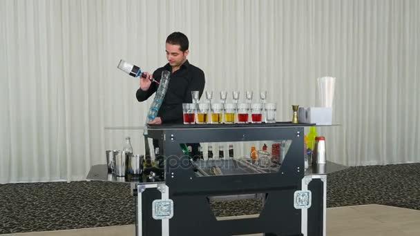 Barkeeper-Show mit Barkeeper Gießen mehrere alkoholische Cocktails Aufnahmen auf einmal