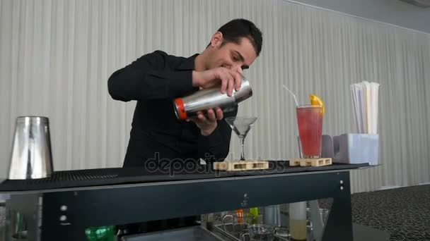 Bartender pouring mixed drink cocktail from shaker into a glass in slow motion