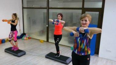 Nők csinál aerobic súlyok kezében szekvencia