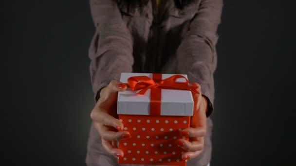 Zblízka s rukama ženy nabízí dárek k narozeninám