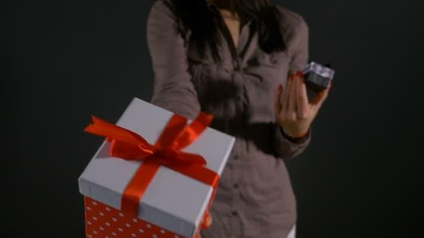 Detailní záběr rukama žena držící velké i malé dárkové krabičky a ukazovat je jako alternativní